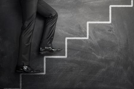 metas: Empresario subiendo las escaleras de carrera dibujados en un pizarr�n negro con copia espacio