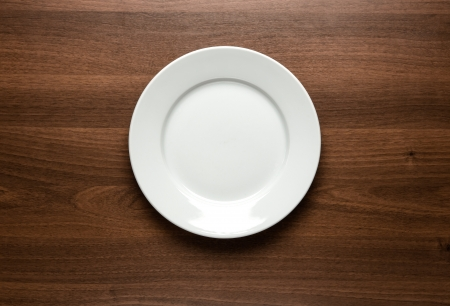 wooden plate: Close up of white empty plate at the wooden table with copy space Stock Photo