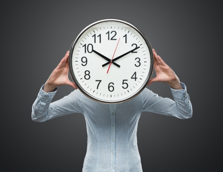 woman with clock: Close up of young businesswoman covering her face with a clock isolated on gray background