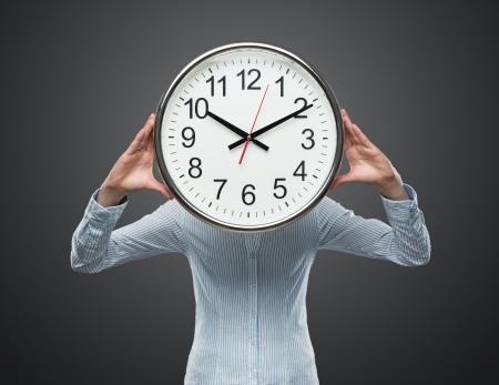 Gros plan de la jeune femme d'affaires couvrant son visage avec une horloge isolé sur fond gris