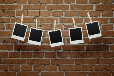 Five instant blank photographs hanging on a clothesline over brick wall with clipping path for the inside of the frames Stock Photo - 18630639