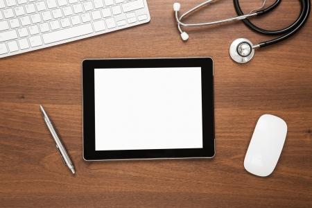 doctor: Primer plano de la tableta digital en blanco en el escritorio m�dico s con trazado de recorte para la pantalla Foto de archivo
