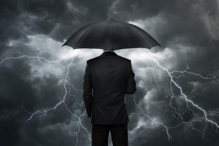 Problemas en el futuro, hombre de negocios con paraguas de pie delante de las nubes tormentosas Foto de archivo