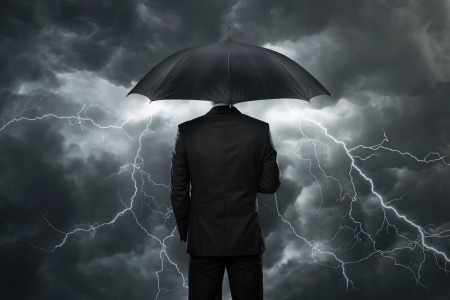 savings risk: Trouble ahead, Businessman with umbrella standing in front of stormy clouds