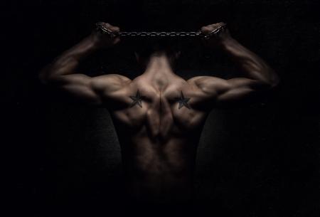 muskeltraining: St�rke, R�ckansicht von muskul�ren Sport Mann streckte �ber dunklen konkreten Hintergrund Lizenzfreie Bilder