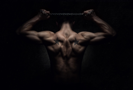 arm muscles: Strength, rear view of muscular sports man stretching out over dark concrete background
