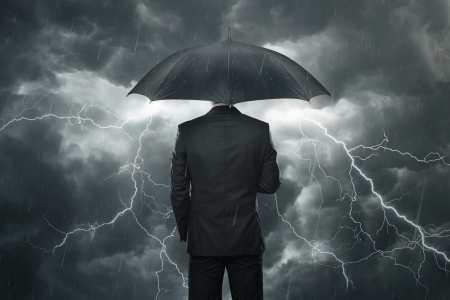 protection risks: Trouble ahead concept, Businessman with umbrella standing in the rain