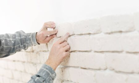 Home improvement, close up of a specialist installing brick wall tiles with copy space photo