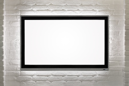 Blank modern flat screen TV at the white brick wall with copy space Stock Photo