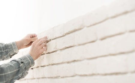 renovating: Home improvement, close up of a specialist installing brick wall tiles with copy space Stock Photo