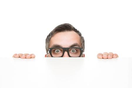geek: Asomándose divertida del empollón de detrás del escritorio aislado en el fondo blanco, con copia espacio