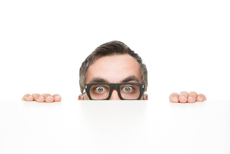 peek: Funny nerd peeking from behind the desk isolated on white background with copy space Stock Photo