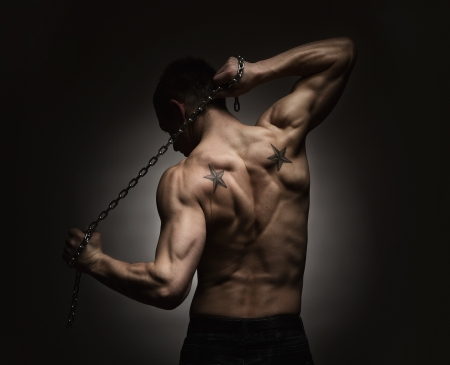 muscular body: Rear view of muscular sports man stretching out over dark background