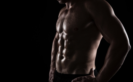 body building: Close up of perfect male body isolated on black background with copy space