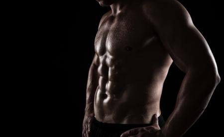 fitness: Primer plano de un cuerpo perfecto hombre aislado en el fondo negro con copia espacio Foto de archivo