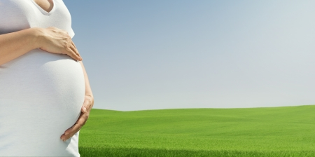 Close up of pregnant woman relaxing at the empty sunny field with copy space