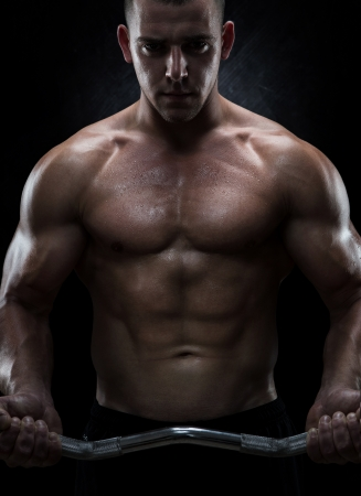 body building: Close up of young muscular man lifting weights over dark background Stock Photo