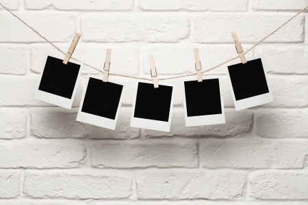 antique frame: Blank photos hanging on a clothesline over brick wall background with copy space