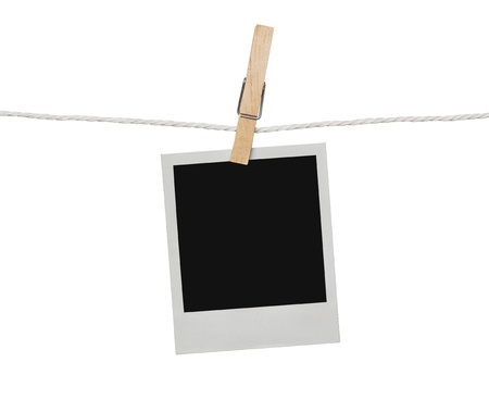Blank photograph hanging on the clothesline isolated on white background with clipping path for the inside of the frame photo