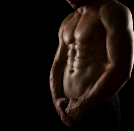 man lifting weights: Close up of perfect male body isolated on black background with copy space