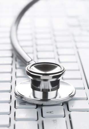 zdraví: Zblízka stetoskop na klávesnici počítače s kopií vesmíru