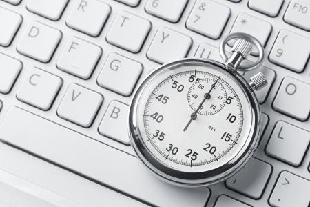 コピー スペースを持つノート パソコンのキーボード上のアナログのストップウォッチのクローズ アップ 写真素材