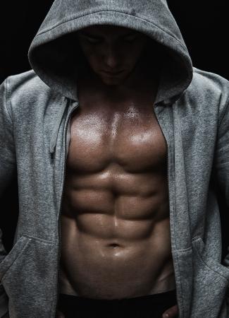 levantar pesas: Primer plano de hombre musculoso joven después del entrenamiento deportivo