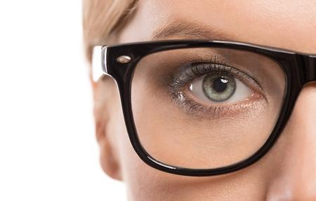 白い背景で隔離の眼鏡との女性の目のクローズ アップ