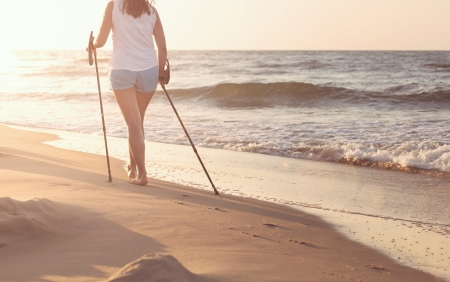 nordic walking: Close up of female nordic walking on a beach at the sunset