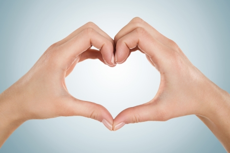 Close up of female hands form heart shape isolated on blue background