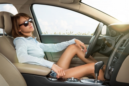 Leasing: Close up of pretty young girl with sunglasses relaxing in the brand new luxury car