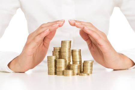 konzepte: Sparen Schutz, close up der weiblichen Händen bedeckt Stapel von goldenen Münzen