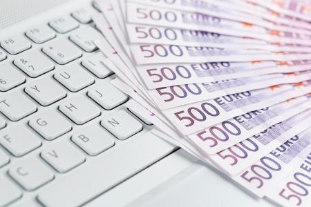 earn money online: European paper currency on the computer keyboard