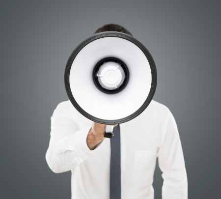 Announcement, young businessman shouting on the megaphone isolated on gray background
