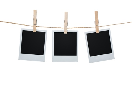 Blank photos hanging on a clothesline isolated on white background Standard-Bild