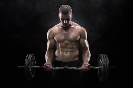 фитнес: Крупным планом молодой мускулистый человек, отмены весов на темном фоне