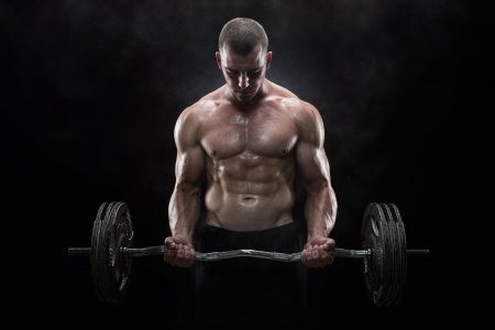 heavy lifting: Close up of young muscular man lifting weights over dark background Stock Photo
