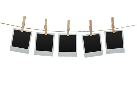 strings: Five blank photos hanging on the clothesline isolated on white background with clipping path for the inside of the frames
