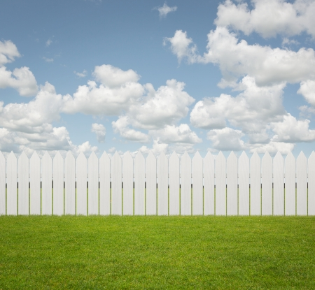 front or back yard: Close up of white fence on the grass with copy space