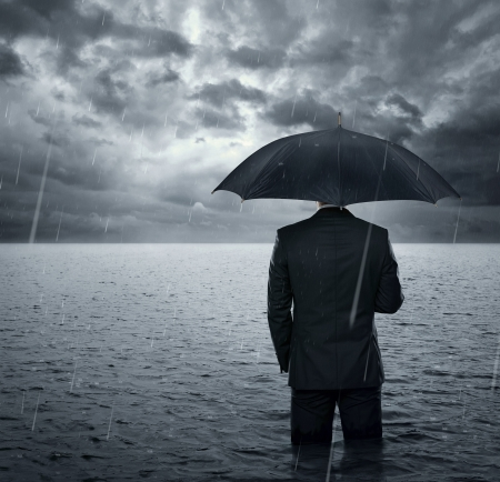 economy: Businessman standing in the dramatic ocean before storm