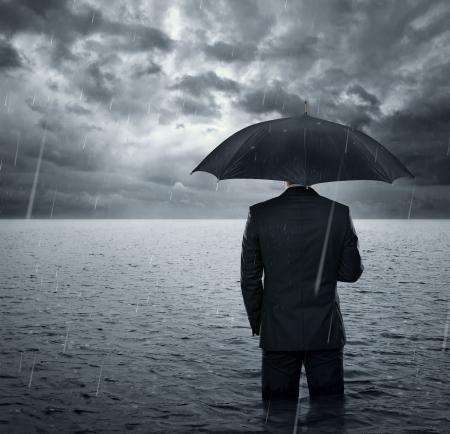 lluvia paraguas: Empresario de pie en el océano dramático antes de la tormenta