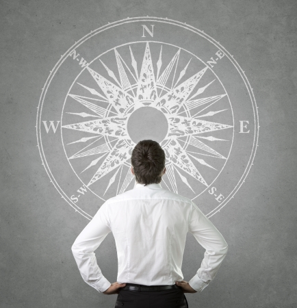 compass rose: Confused, young businessman looking at wind rose drawn on the concrete wall Stock Photo