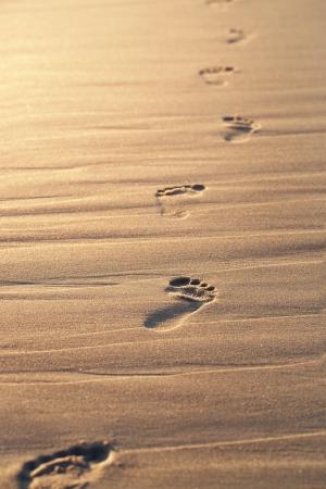 Close-up van voetafdrukken op het strand zand op de zonsondergang met een kopie ruimte