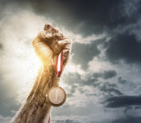 reward: Success, male hand rise up a gold medal against the dramatic sky with copy space Stock Photo