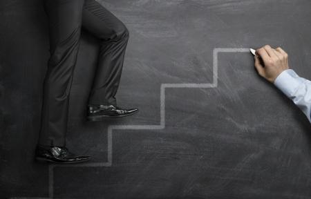 escaleras: Empresario subiendo por los escalones de la carrera en una pizarra negro