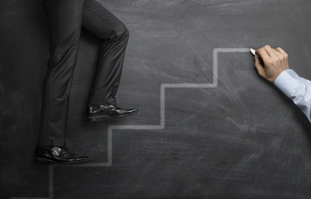 Businessman climbing the career steps drawn on a black chalkboard Archivio Fotografico