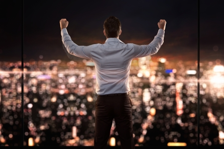 Koning van de wereld, jonge succesvolle zakenman in de voorkant van de stad bij nacht
