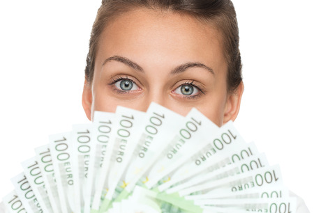Close up of young happy woman holding pile of money isolated on white background Stock Photo