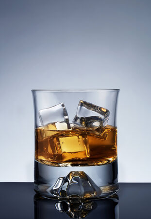 Glass of whiskey on the rocks over blue background with copy space photo