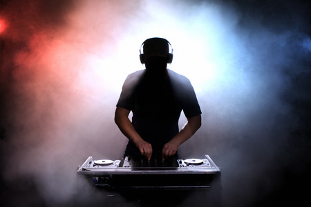 disk jockey: Disc jokey silhouette over illuminated smoke background